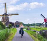 Fietsers op fietspad Nedereindsevaart met molens van Zuylen.n uitbater Jeroen Verbraeken bij Werk bij Maarsseveen.